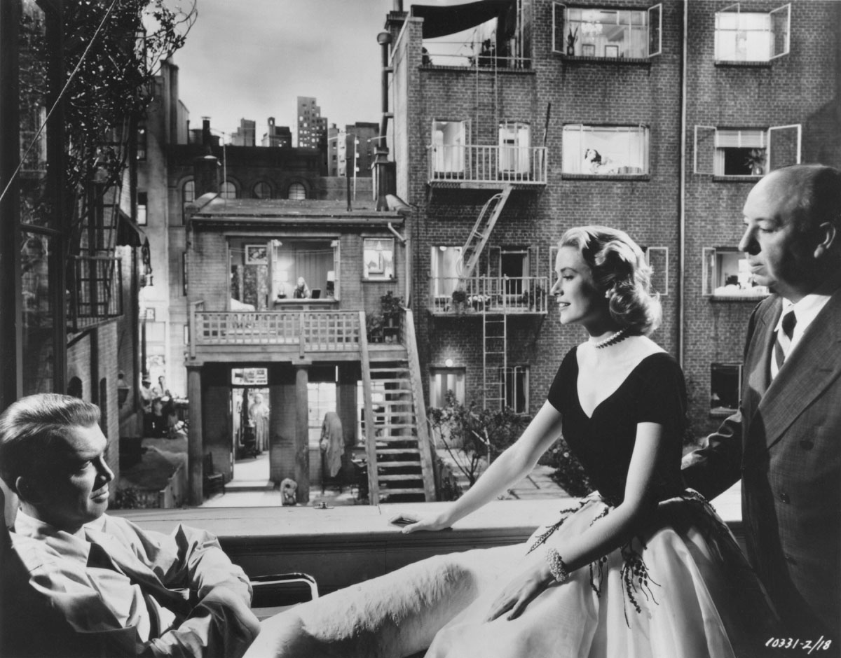 James Stewart, Grace Kelly, and Alfred Hitchcock on the set of REAR WINDOW, 1954